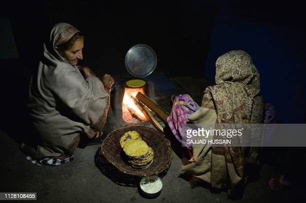 TOPSHOT Indian woman prepare food for their family at their home which was damaged by a mortar shell at Kalal village near Nowshera in Jammu region...