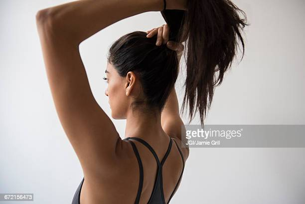 indian woman putting hair in ponytail - haar naar achteren stockfoto's en -beelden