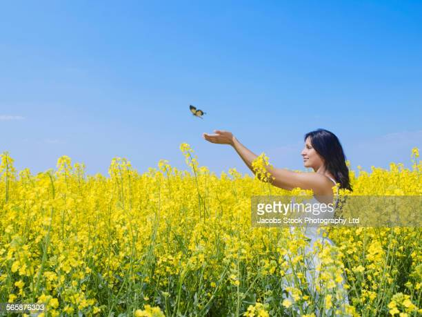 Indian woman reaching for butterfly in field of flowers