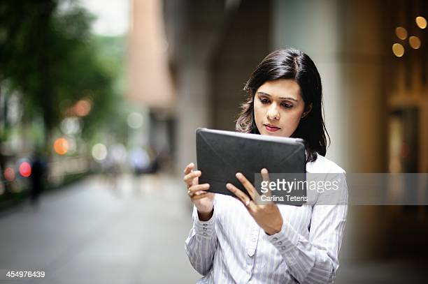 Indian woman reading from a tablet on the street
