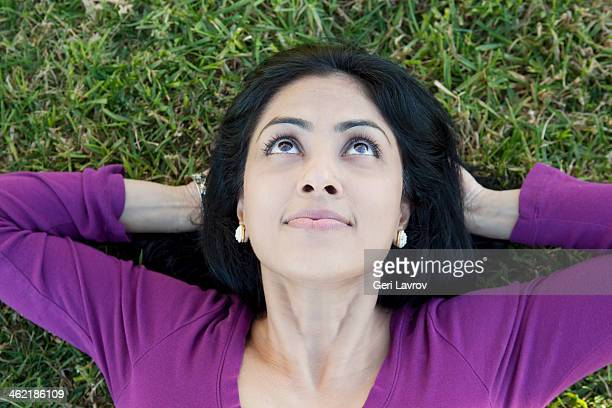 Indian woman relaxing on grass