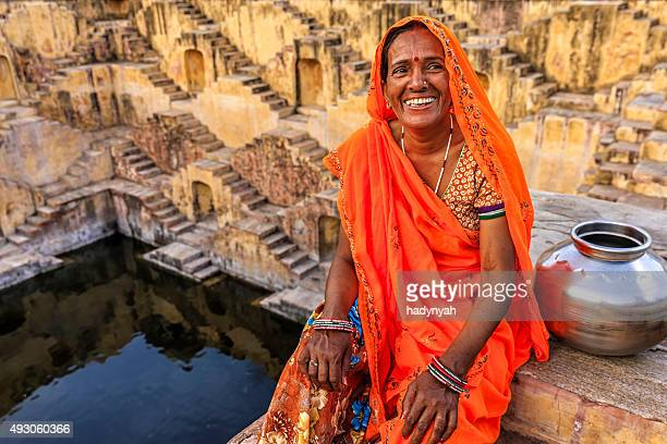 indian woman resting inside stepwell in village near jaipur, india - stepwell stock photos and pictures