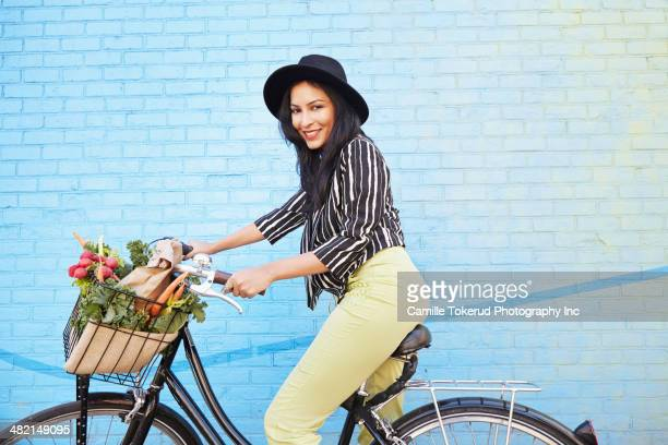 Indian woman riding bicycle along brick wall