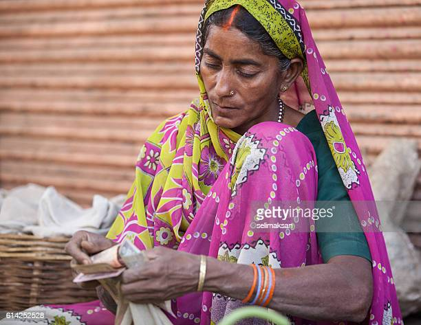 Indian woman seller in farmers market counting money