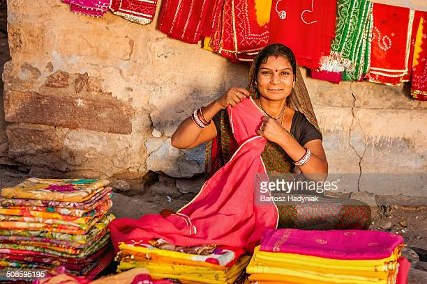 Indian woman selling colorful fabrics on market