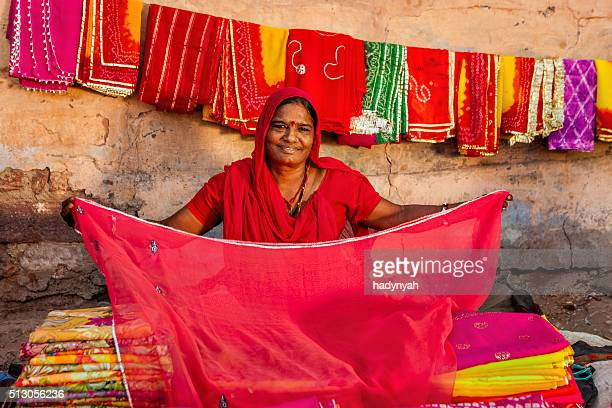 Indian woman selling colorful fabrics