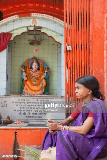 Indian woman sitting by icon of Shiva