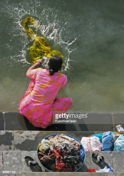 Indian woman sitting on a ghat washing clothes saris in Lake Pichola on January 06 2008 in Udaipur India