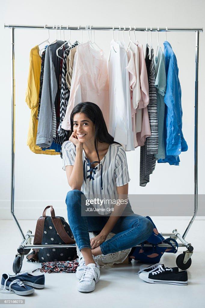 Indian woman sitting on clothing rack : Stock Photo