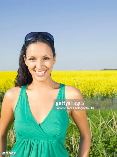 Indian woman smiling in field of flowers