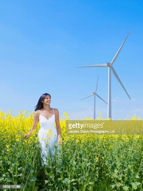 Indian woman standing in field near wind turbines
