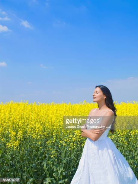 Indian woman standing in field of flowers
