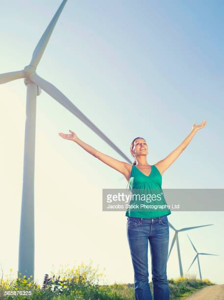 Indian woman standing under wind turbines