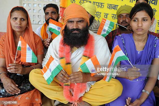 Indian woman Sukhpreet Kaur the wife of Indian prisoner Sarabjit Singh currently in a Pakistan jail and his daughter Poonam pose with Baba Bajrangee...