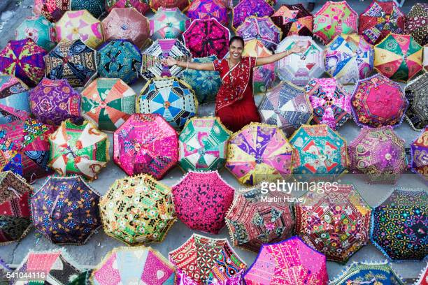 indian woman surrounded by colorful umbrellas - abundance stock pictures, royalty-free photos & images