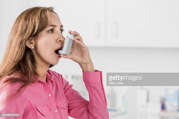 Indian woman using inhaler in doctor's office