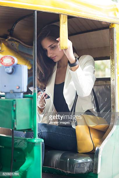 indian woman using smart phone while riding in auto rickshaw. - rickshaw stock pictures, royalty-free photos & images