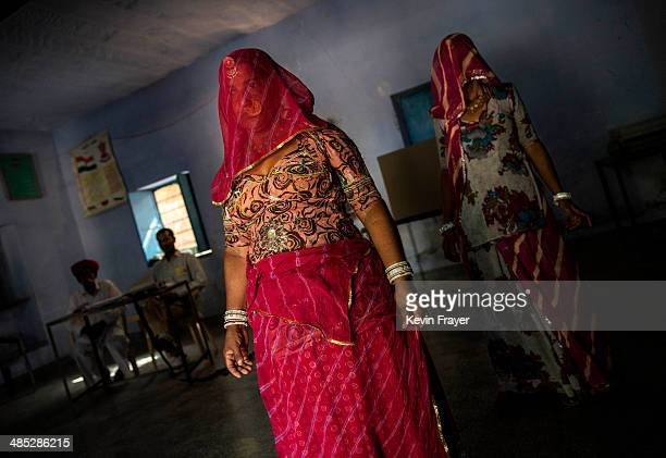 Indian woman walk away after casting their ballots at a polling station on April 17 2014 in the Jodhpur District in the desert state of Rajasthan...