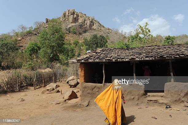 Indian woman walks towards her home adorned with a solar panel with which to generate electricity in the remote hamlet of Nilwas in Banaskantha...