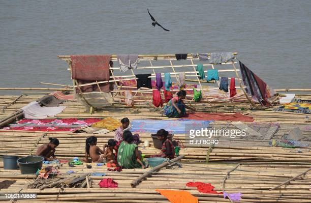 TOPSHOT Indian woman wash their clothes while sitting on floating bamboo for sale along the river Brahmaputra in Guwahati on October 15 2018