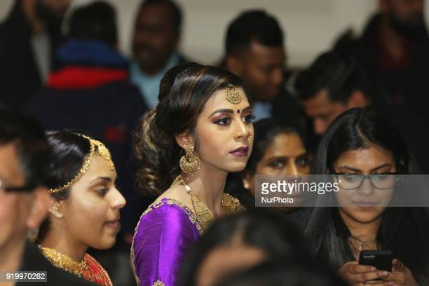 Indian woman watches as models showcase elegant designer bridal sarees during a South Asian bridal fashion show held in Toronto Ontario Canada on...