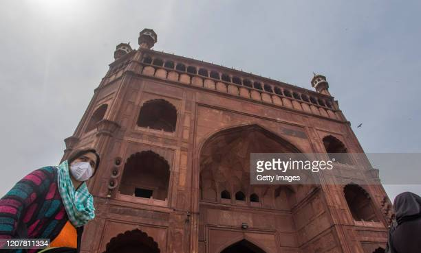 Indian woman wearing a protective mask waits outside the historic Jama Masjid amid the government imposing restriction on assembly of more than 20...