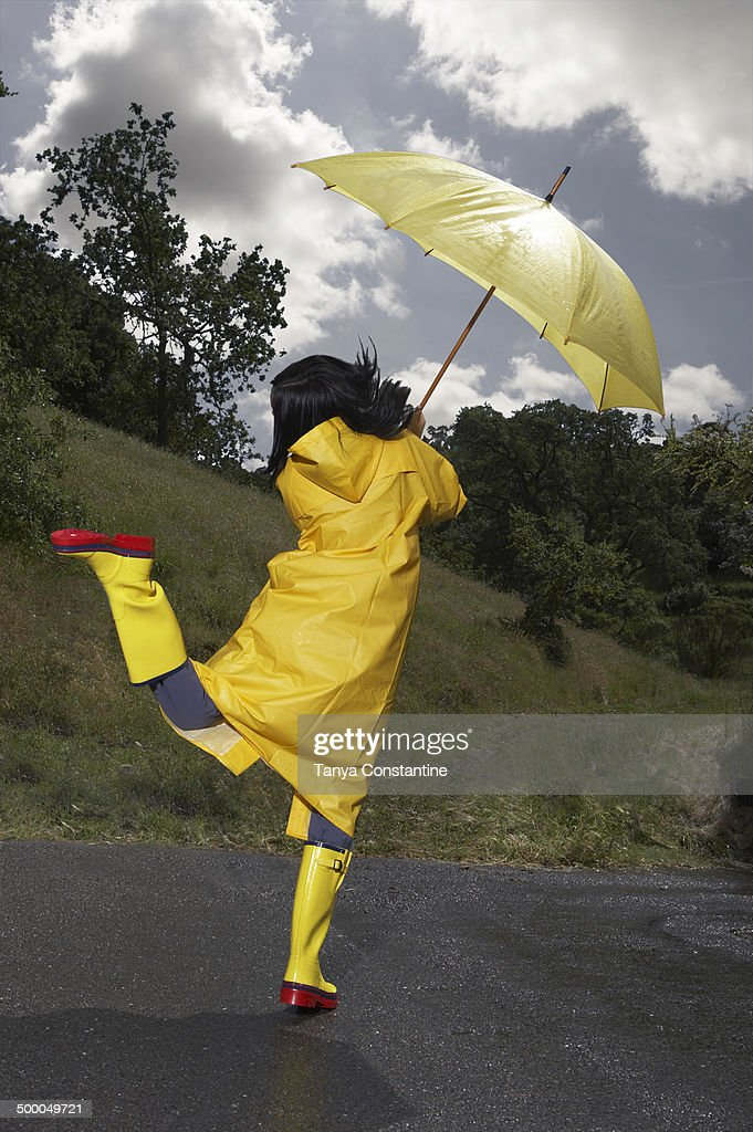 Indian Woman Wearing Raincoat And Rainboots With Umbrella Stock