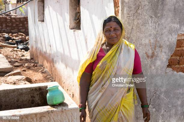Indian woman with a traditional scarf she stands at the side of a bio gas installation As Hindu woman she is signed with a bindi what means that she...