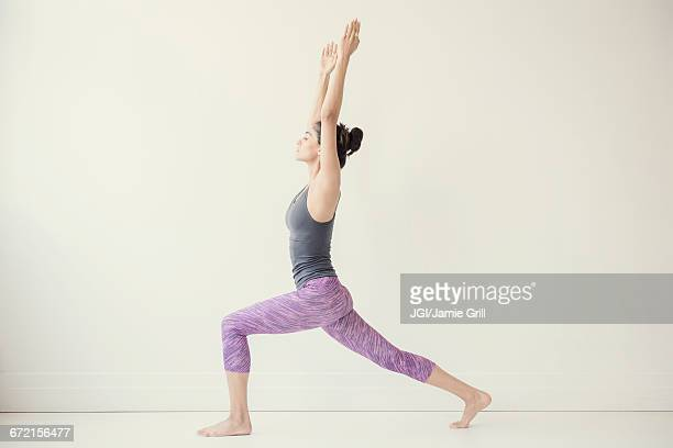 indian woman with arms raised yoga pose - yoga stockfoto's en -beelden