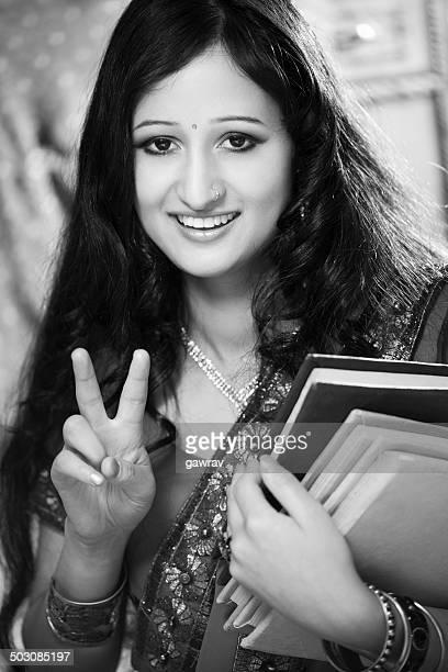 Femme indienne avec des livres présentant deux doigts pour exprimer succès.