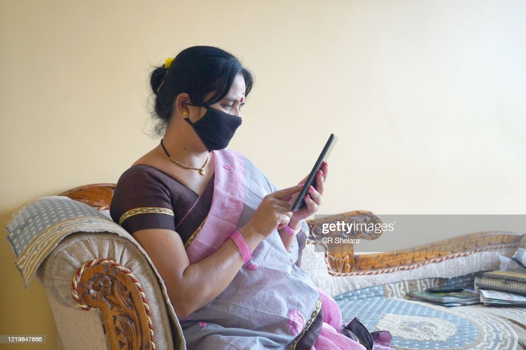 Indian woman with face protective mask reading news on tablet. : Stock Photo