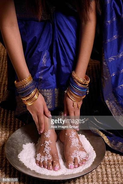 indian woman with feet in salt scrub - indian female feet stock pictures, royalty-free photos & images