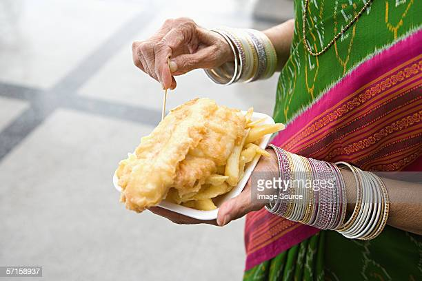 indian woman with fish and chips - carton stock photos and pictures