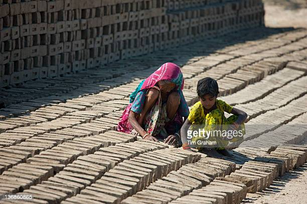 Indian woman with grandchild drying bricks made from clay at Khore Bricks Factory Rajasthan Northern India