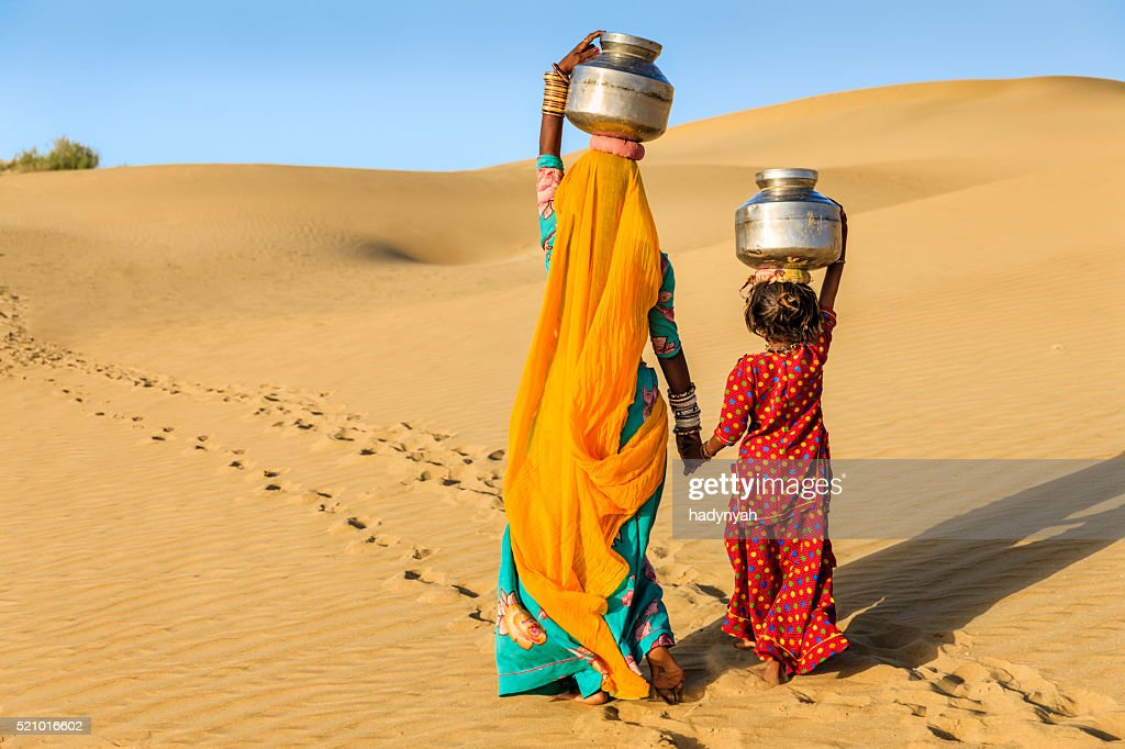 Indian woman with little daughter carrying water from well : Stock Photo