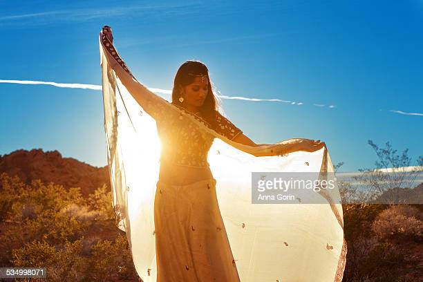 indian woman with shawl outstretched at sunset - sari fotografías e imágenes de stock