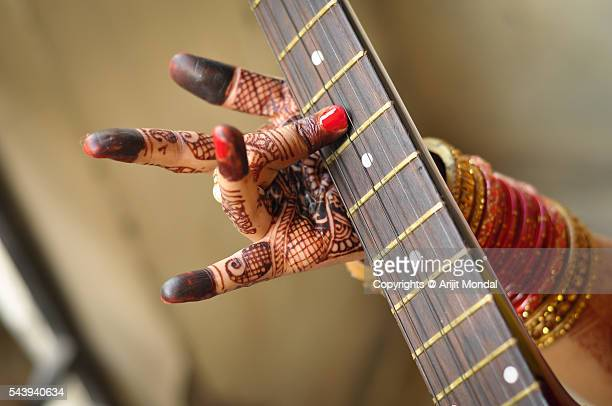 Indian woman's hand with beautiful henna tattoo and guitar