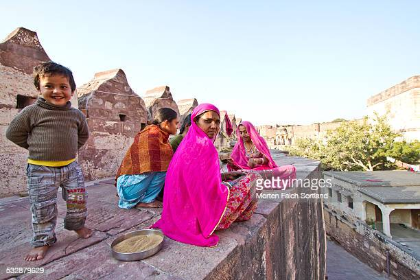 Indian women and a young boy atop an old stone wall at Meherangarh Fort in Jodhpur