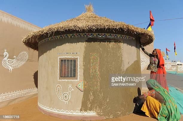 Indian women apply mud to a hut in Dhordo village close to the IndiaPakistan border some 500 kms from Ahmedabad on December 17 2011 The Rann Utsav...