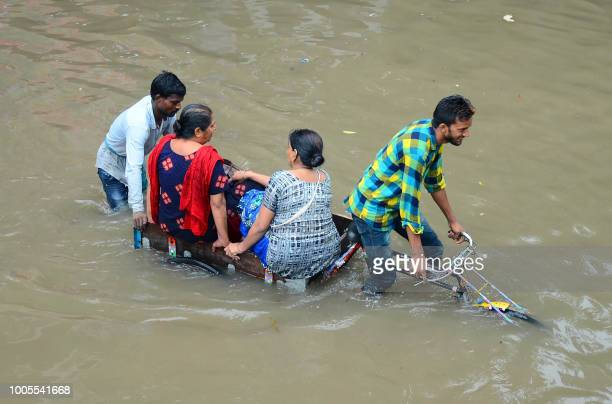 Indian women are transported on a bicycle cart on a flooded road following heavy rain in Mathura in Uttar Pradesh state on July 26 2018