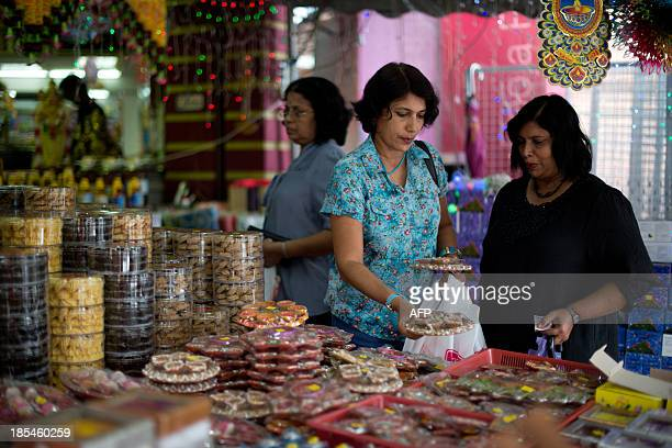 Indian women browse cookies ahead of the upcoming Diwali festival celebrations in the Brickfields area also known as Little India in Kuala Lumpur on...
