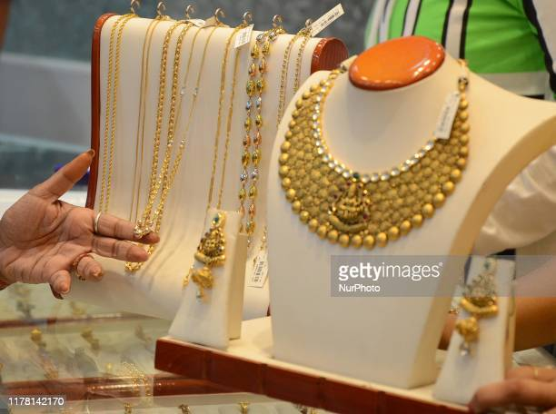 Indian women buying Gold jewellery in a shop during the Diwali festival called Dhanteras in Kolkata India on Friday 25th October 2019 On the occasion...
