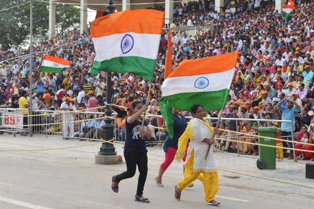 Indian women carry Indian flags during the beating retreat ceremony at the India Pakistan Wagah Border post in Amritsar on August 2 2017 / AFP PHOTO..