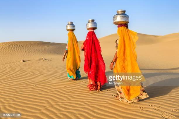 indiska kvinnor bär på sina huvuden vatten från lokala väl - hinduism bildbanksfoton och bilder