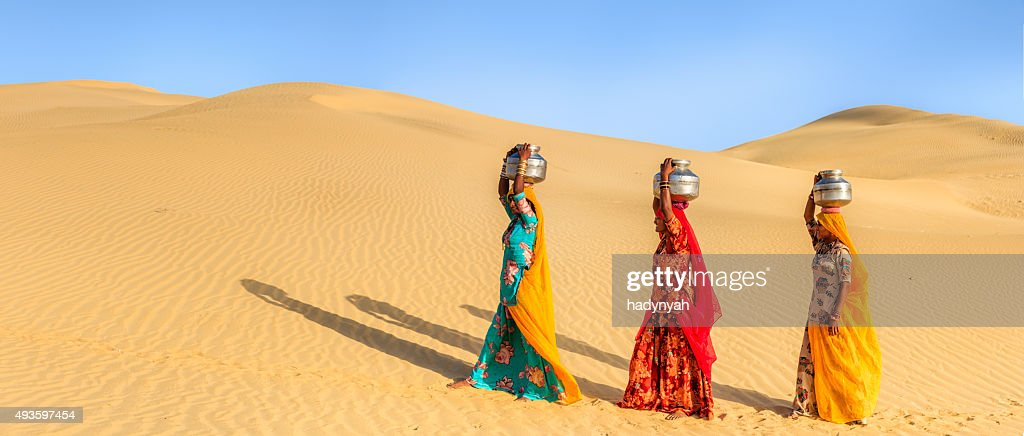 Indian women carrying on their heads water from local well : Stock Photo