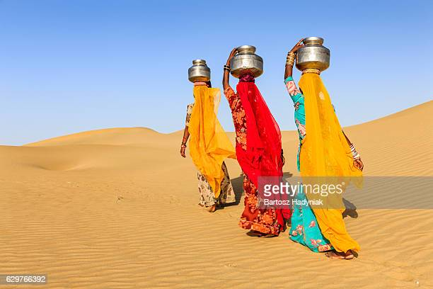 indian women carrying on their heads water from local well - rajasthan stock pictures, royalty-free photos & images