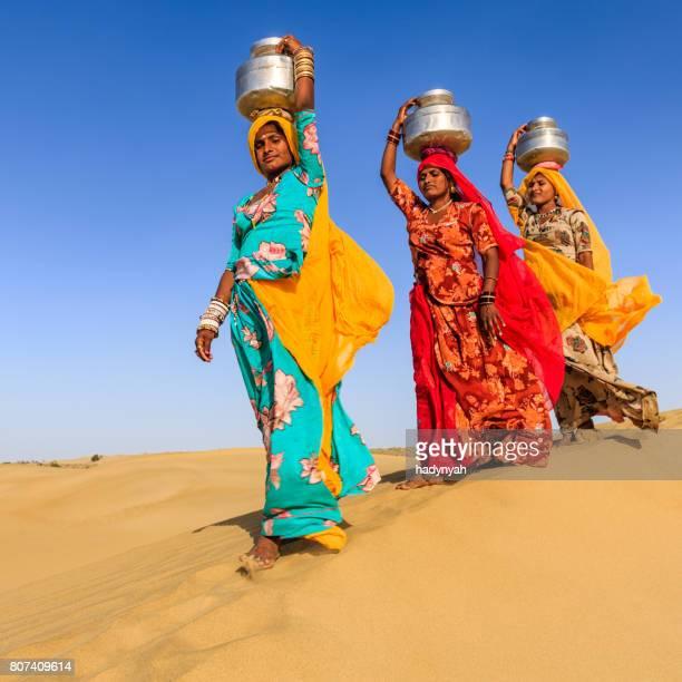 Indische Frauen tragen von Wasser auf den Kopf von lokalen gut