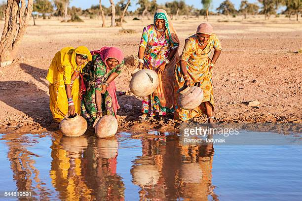 Indian women carrying water from lake