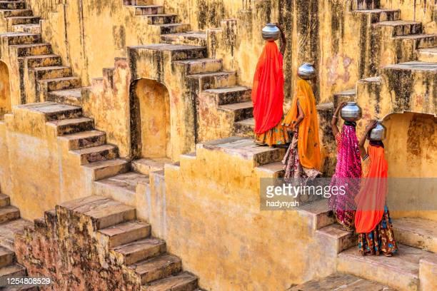indiska kvinnor som transporterar vatten från stepwell nära jaipur - stepwell bildbanksfoton och bilder