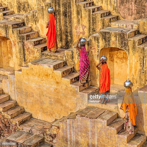 indian women carrying water from stepwell near jaipur - step well stock photos and pictures